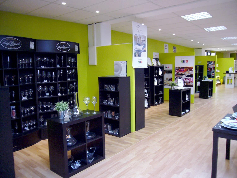 photo d'un show room aavec des meubles noir et peinture murale verte