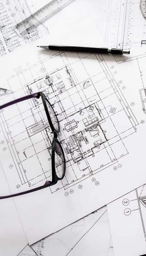 Photo d'un plan d'architecte avec des lunettes et un crayon posés dessus